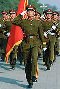 Soldiers salute while marching in Tiananmen Square with a red flag in Beijing (Peking), China