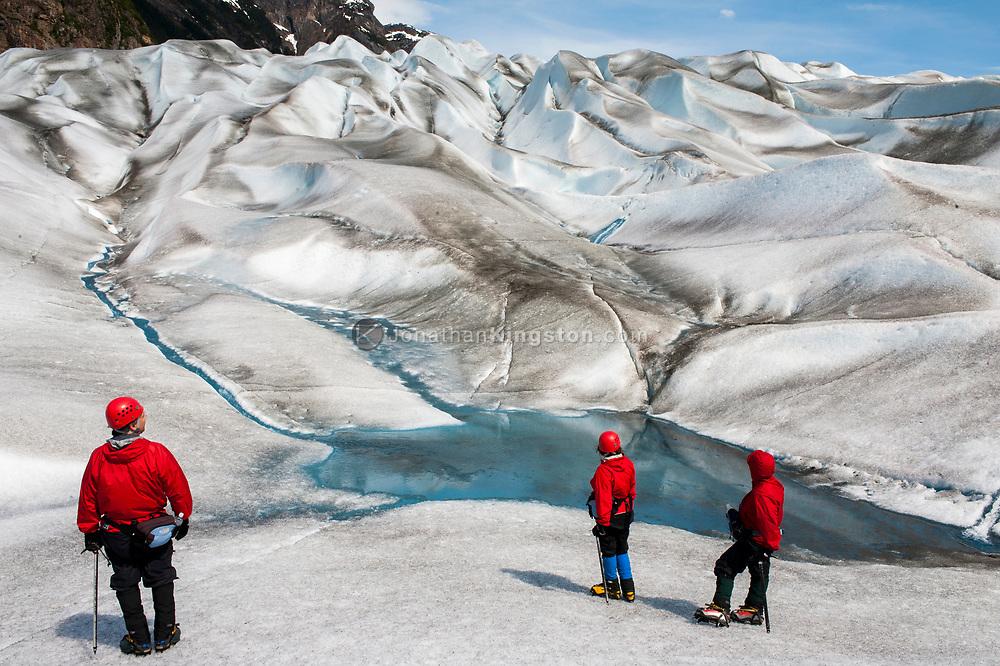 Three crampon clad tourists walk on a glacier near Juneau, Alaska.