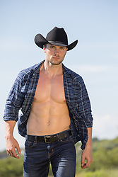 cowboy with open shirt walking on a ranch