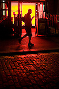 Man walking past strong red lighting whiile using mobile phone handset.