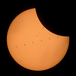 This composite image, made from seven frames, shows the International Space Station, with a crew of six onboard, as it transits the Sun at roughly five miles per second during a partial solar eclipse, Monday, Aug. 21, 2017 near Banner, Wyoming. Onboard as part of Expedition 52 are: NASA astronauts Peggy Whitson, Jack Fischer, and Randy Bresnik; Russian cosmonauts Fyodor Yurchikhin and Sergey Ryazanskiy; and ESA (European Space Agency) astronaut Paolo Nespoli. A total solar eclipse swept across a narrow portion of the contiguous United States from Lincoln Beach, Oregon to Charleston, South Carolina. A partial solar eclipse was visible across the entire North American continent along with parts of South America, Africa, and Europe.  Photo Credit: (NASA/Joel Kowsky)  Please note: Fees charged by the agency are for the agency's services only, and do not, nor are they intended to, convey to the user any ownership of Copyright or License in the material. The agency does not claim any ownership including but not limited to Copyright or License in the attached material. By publishing this material you expressly agree to indemnify and to hold the agency and its directors, shareholders and employees harmless from any loss, claims, damages, demands, expenses (including legal fees), or any causes of action or allegation against the agency arising out of or connected in any way with publication of the material.