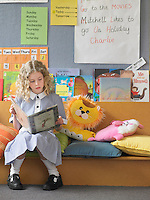 Elementary schoolgirl reading book on couch in classroom