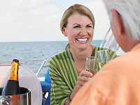Middle-aged couple drinking champagne on yacht