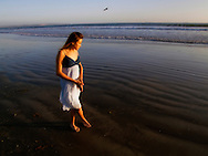 Young woman standing on beach near water.
