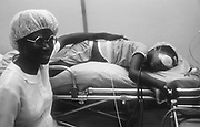 The Orbis Flying Eye Hospital Recovery. Local nurse watches over a young boy after sight saving eye operation