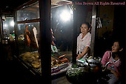 A woman street vendor is working at night selling meat on a city street in Kampong Cham, Cambodia.