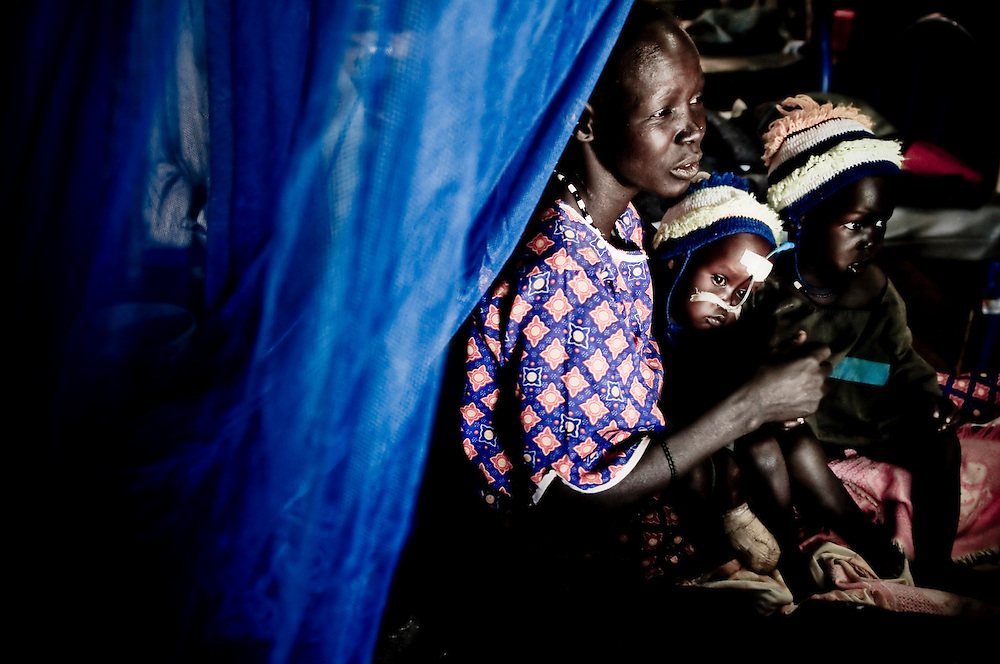 A refugee from Northern Sudan cares for her malnourished child, in an Aweil hospital, run jointly by MSF and the Sudanese Ministry of Health. The central town of Aweil sits just below the hotly contested border between North and South Sudan. A severely challenged health care infrastructure will be one of many obstacles a newly independent South Sudan will face should they separate from the North. (© William B. Plowman)