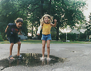 Michelle Goelle and her cousin Gabe splashing in a puddle, she saved Gabe from drowning when their dinghy capsized in some rapids, she broke her arm on some rocks whilst saving him, Detroit, USA, 2003