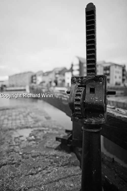 Closeup of the mechanism of a lock gate, using selective focus, with the new buildings of Bridgwater quay in the background.