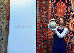 "© Licensed to London News Pictures. 28/09/2012. London, UK Auction room staff hold A highly important Fatimid white-ground lustre pottery jar from Egypt dated 10th/11th century. The jar is expected to fetch 300,000-500,000GBP. Sotheby's Auction rooms in New Bond Street, London hold a photo call for their upcoming ""arts of the Islamic World"" auction which is expected to realise in the region of 5 million GBP . Photo credit : Stephen Simpson/LNP"
