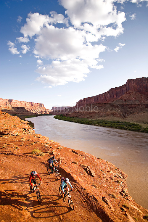 Mountain Bikers Wyatt Noble (age 15), Katie Caviccio and Brad Barlage riding the White Rim Trail along the Green River inCanyonlands National Park, Utah USA.