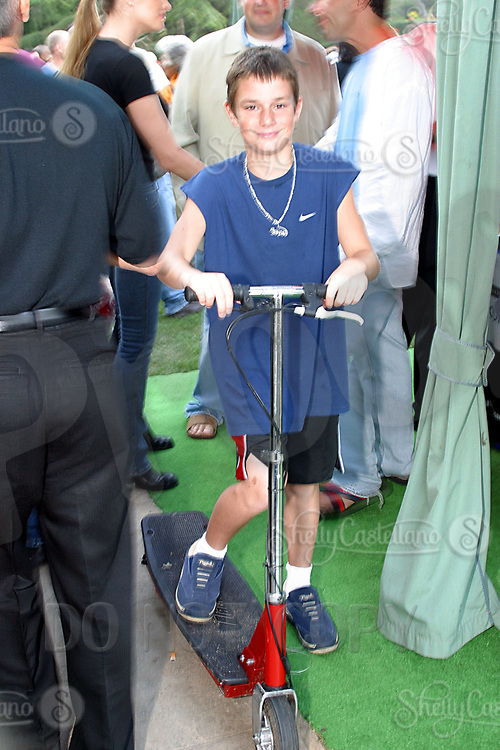 Jul 09, 2002; Los Angeles, CA, USA; HUGH HEFNER's 10year old son COOPER HEFNER rides around his back yard guests on an electric scooter as SUGAR RAY LEONARD BOXING first year anniversary was celebrated with a live fight night on ESPN2 from the Playboy Mansion in Holmby Hills.  Over 350 invited guests attended the cocktail reception and showdown in the back yard of Playboy HUGH HEFNER's 5 1/2 acre estate. <br /> Mandatory Credit: Photo by Shelly Castellano/ZUMA Press.<br /> (&copy;) Copyright 2002 by Shelly Castellano