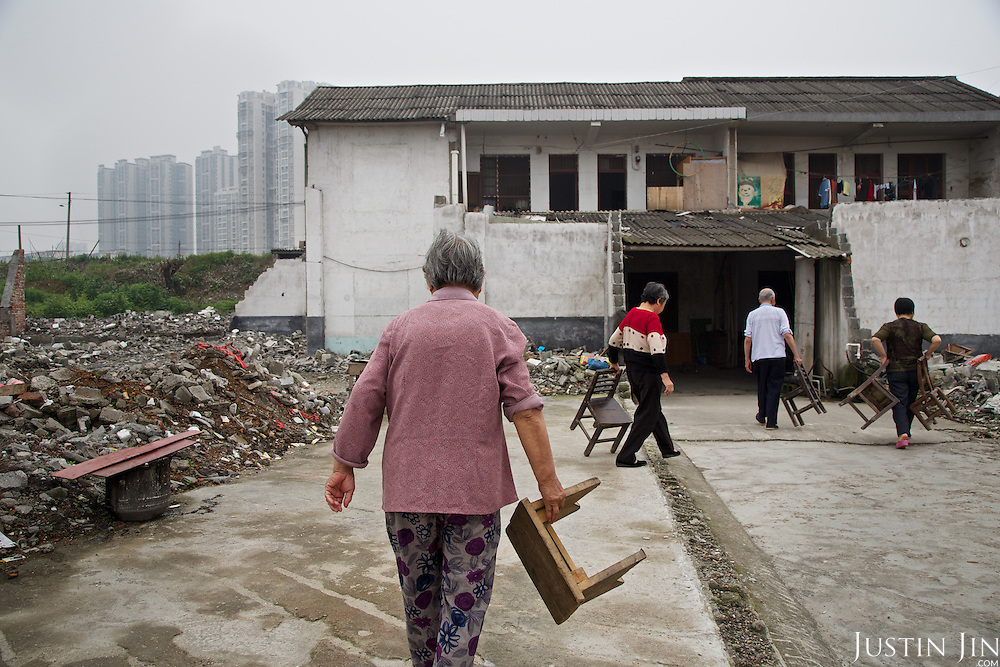 Elderly people in southern China walk to their home that is about to be demolished for modern high rise. <br /> <br /> China is pushing ahead with a dramatic, history-making plan to move 100 million rural residents into towns and cities over six years &mdash; but without a clear idea of how to pay for the gargantuan undertaking or whether the farmers involved want to move.<br />