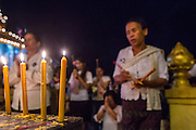 02 FEBRUARY 2013 - PHNOM PENH, CAMBODIA:   Candles burn in honor of former King Norodom Sihanouk at a small shrine near the Royal Palace in Phnom Penh. Much of Phnom Penh has been shut down to honor former King Norodom Sihanouk, who ruled Cambodia from independence in 1953 until he was overthrown by a military coup in 1970. Only bars, restaurants and hotels that cater to foreign tourists are supposed to be open. The only music being played publicly is classical Khmer music. Sihanouk died in Beijing, China, in October 2012 and will be cremated during a state funeral royal ceremony on Monday, Feb. 4.   PHOTO BY JACK KURTZ