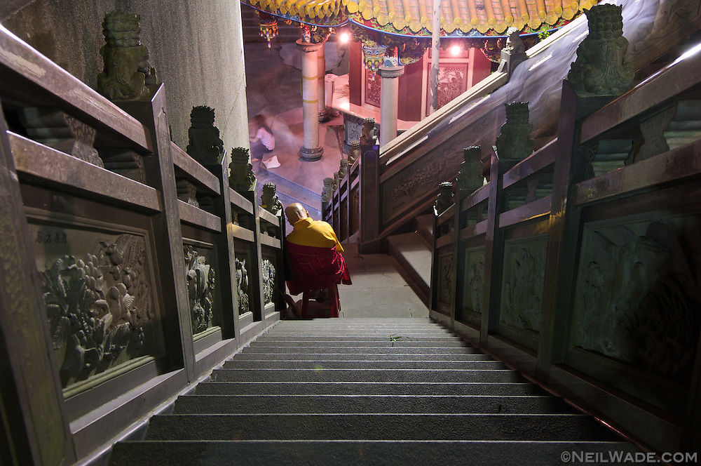 An elderly Buddhist monk sleeps as he collects alms at a temple in Taipei. Taiwan.