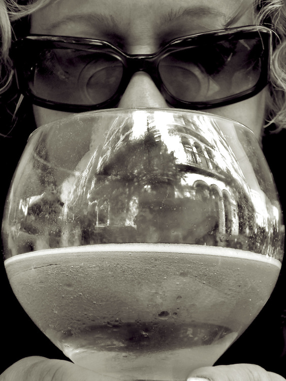 cloeup of woman with glass of beer wearing sunglasses,black and white,verticle