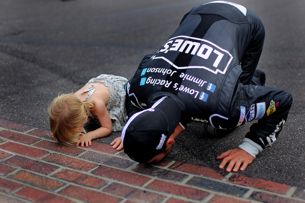 Jimmie Johnson, driver of the #48 Lowe's/Kobalt Tools Chevrolet, kisses the bricks with his daughter Genevieve Marie after winning the NASCAR Sprint Cup Series Crown Royal presents the Curtiss Shaver 400 at the Brickyard at Indianapolis Motor Speedway on July 29, 2012 in Indianapolis, Indiana.