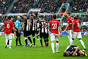 Newcastle United players surround referee Mike Dean after Sean Longstaff (#36) of Newcastle United is fouled during the Premier League match between Newcastle United and Manchester United at St. James's Park, Newcastle, England on 6 October 2019.