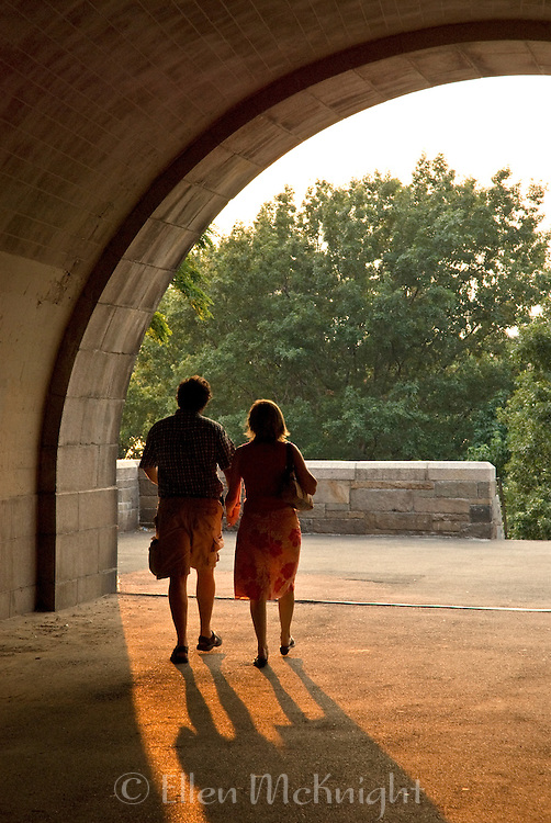 Couple walking into Riverside Park on the West Side of Manhattan at sunset on a summer's evening in New York City, NY