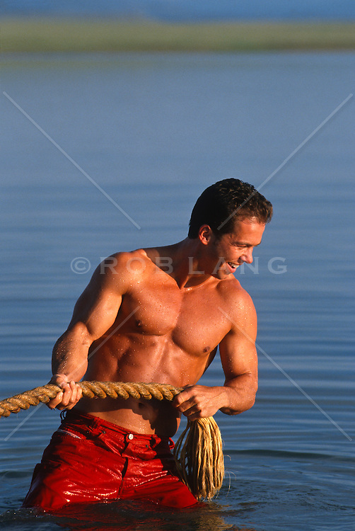 Man in a lake pulling a rope