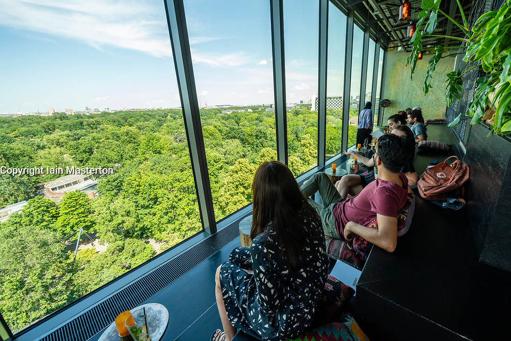 View of customers looking out over Tiergarten in the rooftop Monkey Bar at fashionable 25hours Hotel in Berlin, Germany
