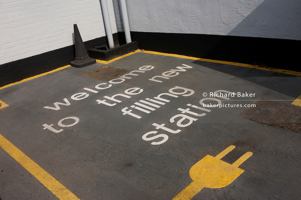 Empty parking space at a Nissan car dealership where their Leaf electric car (EV) can be recharged at a charging point.