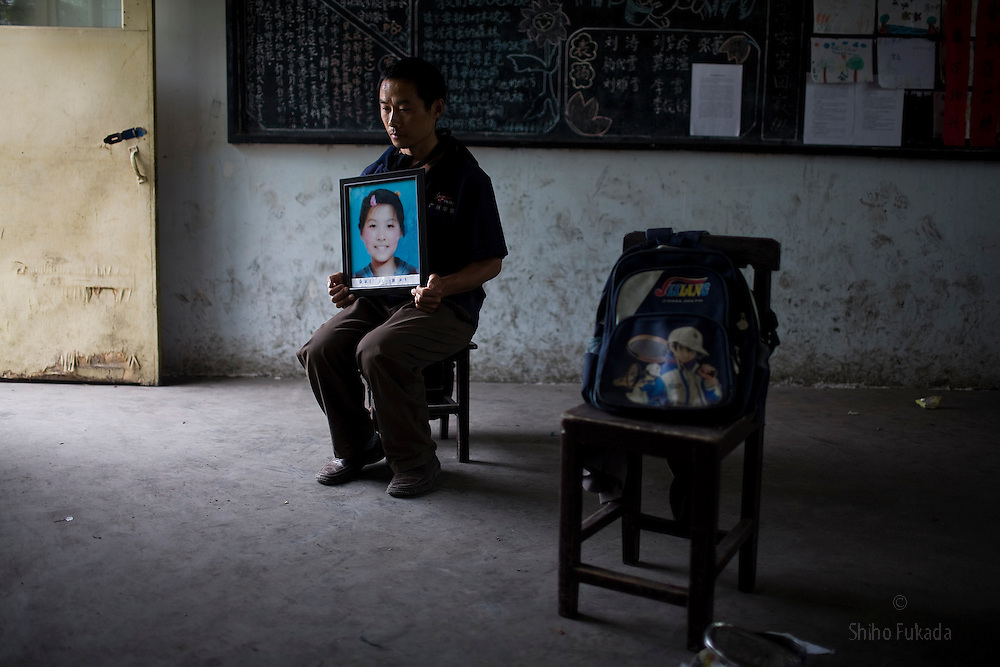 "Zhang Hua Shan, 37, holding a picture of his daughter Zhang Qiu Yue, 12, is seen at Fuxin No.2 Primary  School in Wufu, Sichuan province May 24, 2008.  ""The building is dangerous so they moved the older kids to another shool. I want to know why they put the younger children to this builindg."""