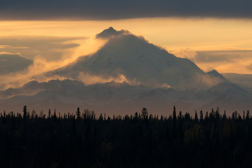 A telephoto view of Mt. Redoubt volcano, during sunset showing high wind and blowing snow on its flanks while venting steam at the top.