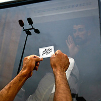 An Iraqi man asks a detainee on a bus for information about his relative moments after the bus departed from Abu Ghraib prison west of the Iraqi capital of Baghdad. The card reads 'Jawad Ahmad, Northern Khark'. Khark is a section of Baghdad. The U.S. military released several hundred prisoners from Abu Ghraib on Friday, keen to show it is improving conditions at the jail where images of U.S. soldiers abusing prisoners have sparked international outrage. May 2004.
