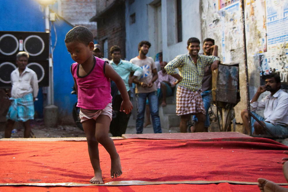 A child dances on a stage while a celebration is under preparation in Saidapet, Chennai, India.