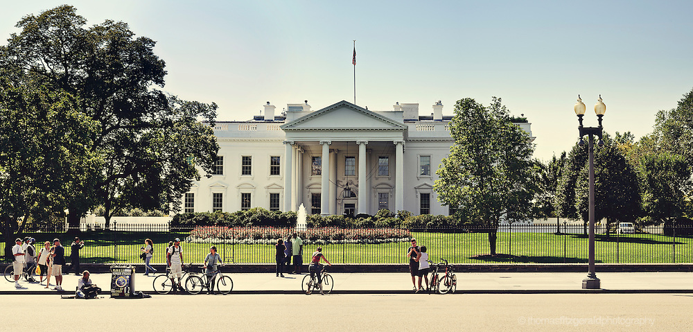 A group of tourists and onlookers stand in front of the Whitehouse, washington DC, USA