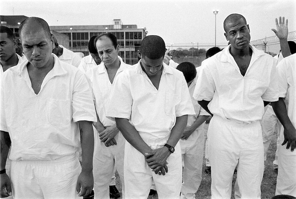 Inmates Santiago Marin, front left, Vera Monico, Larry Gooden, center, and Willie Charleston, right, pray during service in yard at Coffield Prison in Texas where the Bill Glass Ministry appealed to 4200 inmates in a 48 hour blitz to lead them to salvation as born-again Christians.
