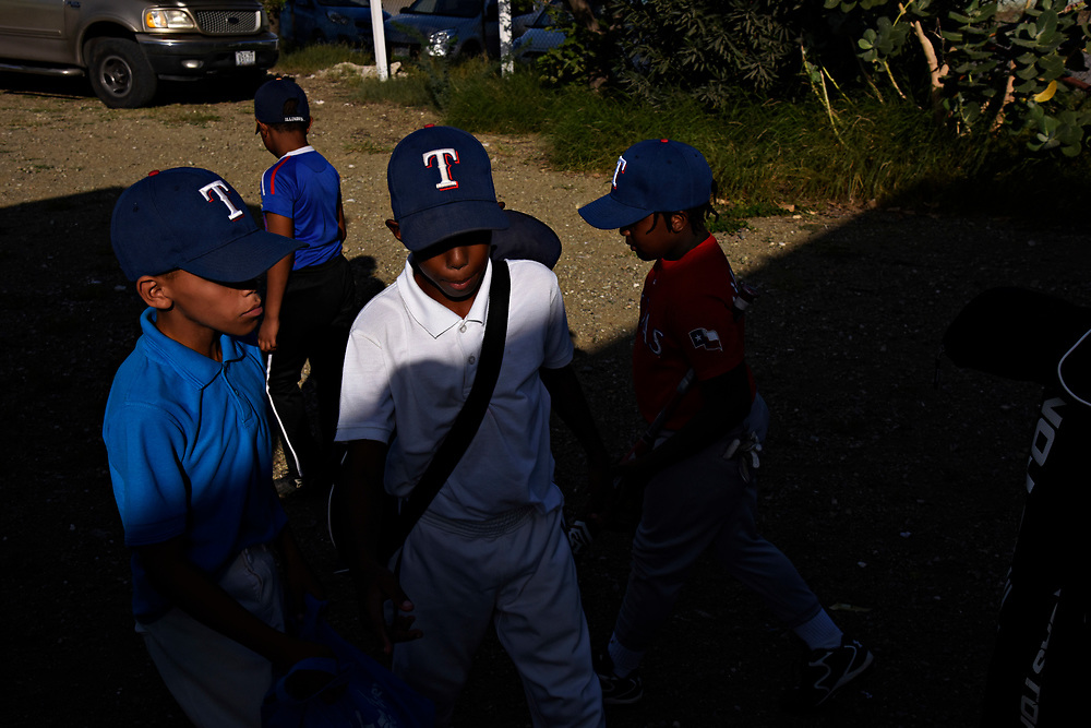 "WILLEMSTAD, CURACAO - DECEMBER 10, 2014: Members of the Marchena Hardware 7-9 year old Liga Vruminga team, which translates to ""league of little ants,"" play behind the dugout until the older boys are off the field. The team wears Texas Rangers hats because Rangers player Jurickson Profar's little brother Jurdrick Profar is on the team. (photo by Melissa Lyttle)"