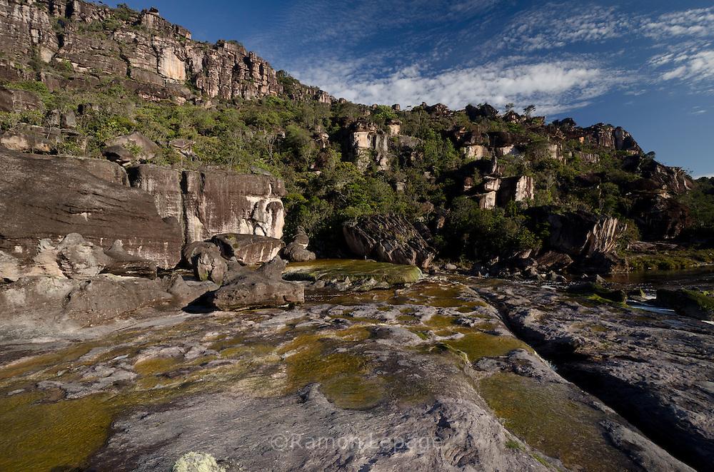 """AUYANTEPUY, VENEZUELA. Rio Churum y vista de la Segunda Murralla.  El Auyantepuy es el mayor de los tepuis del Parque Nacional Canaima. En sus 700 kms2 alberga el salto angel o conocido por lengua indígena Pemon como """"Kerepacupai Vena; es la caída de agua más grande del mundo con sus 979 metros de altura. (Ramon lepage /Orinoquiaphoto/LatinContent/Getty Images)"""