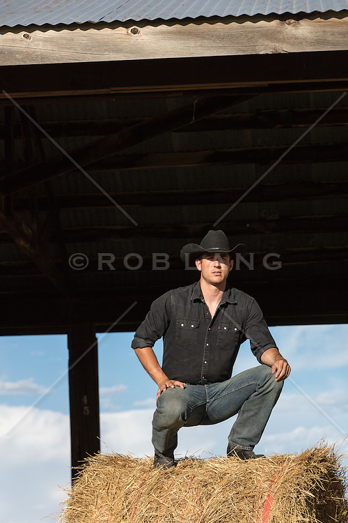 cowboy squatting on a hay bale in a barn at sunset