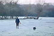 © Licensed to London News Pictures. 29/12/2013. East Bergholt, UK. A womb walks her dog.  Early morning frost and mist on the River Stour at Deadham Vale this morning 29th December 2013. Photo credit : Stephen Simpson/LNP