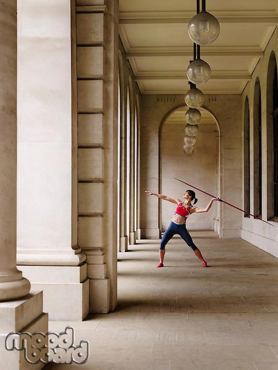 Female athlete throwing javelin in portico