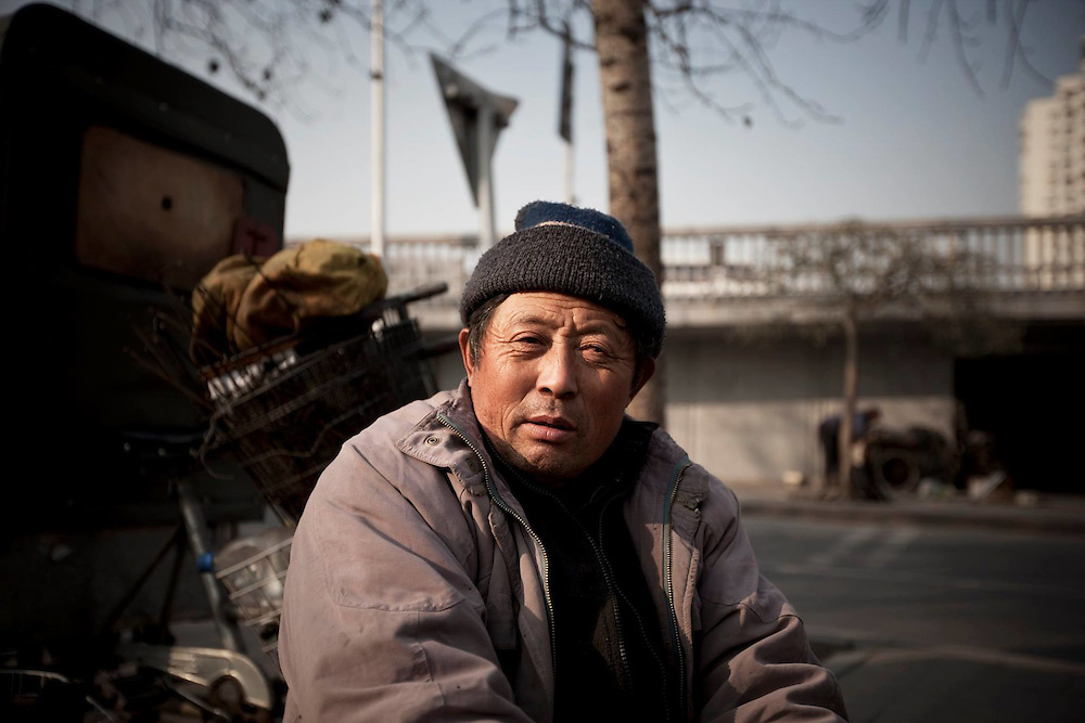 An old migrant worker, repairing bycicles next to a road in Beijing. Around 200 million workers in China are on the 'tramp', erecting the country's shining metropolises as labourers and running the factories as shift workers.
