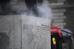"© Licensed to London News Pictures. 08/06/2020. London, UK. A cleaner removes Graffiti from a statue of former British Prime Minister Winston Churchill in Parliament Square, after it was graffitied with the words ""was a racist"" during a Black Lives Matter demonstration In central London. The death of George Floyd, who died after being restrained by a police officer In Minneapolis, Minnesota, caused widespread rioting and looting across the USA. Photo credit: Ben Cawthra/LNP"