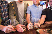 Four white British men line up their drinking glasses on a bar in an English pub in London, United Kingdom.  Two men have been drinking beer and two have been drinking hard liquor spirit drinks. Drinking alcohol in pubs is a fundamental part of British culture.