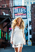 Nashville Senior Portrait of a blonde girl in a white dress smiling and walking through Printers Alley in Downtown Nashville