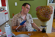 Jake uses a glue gun to stick rhinestones to his drag queen wig.