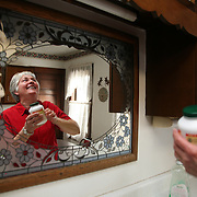 "Farm wife Karen Johnson reaches for a bottle of vitamins in the kitchen of her home in rural Shelby County, Iowa.  The Johnson's take a daily dosage of vitamin E, vitamin C, Calcium, Gluconosime and a low dosage aspirin to help stay healthy.<br /> <br /> Johnson and her husband Bill have been farming for over 55 years, and have no immediate plans for retirement.  <br /> <br /> ""We plan on doing this for another 15 years,"" she said.    Photo by David Peterson"