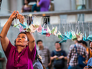 "06 JULY 2015 - BANGKOK, THAILAND: A person hangs a paper dove during a protest called ""Wing of Peace"" at Thammasat University/ More than 100 people gathered at Thammasat University in Bangkok Monday to show support for 14 students arrested two weeks ago. The students were arrested for violating orders against political assembly. They face criminal trial in military courts. The students' supporters are putting up ""Post It"" notes around Bangkok and college campuses up country calling for the students' release.      PHOTO BY JACK KURTZ"