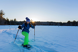 A teenage girl snowshoes across a frozen beaver pond at sunset in Epping, New Hampshire.