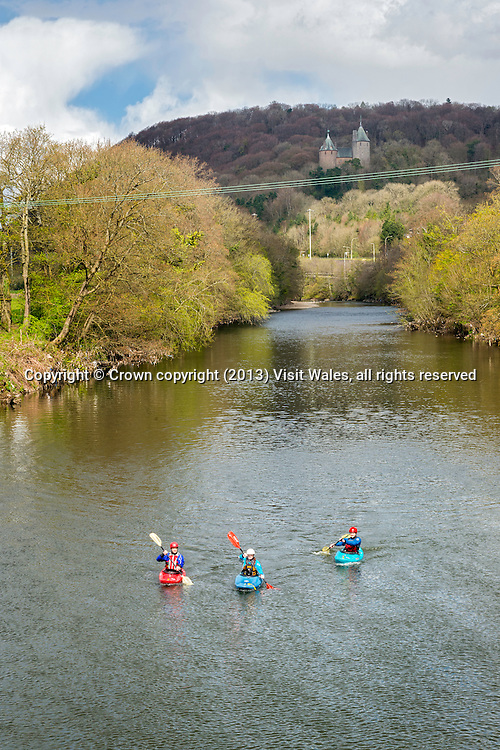 Kayakers on river above Radyr Weir with Castell Coch in background <br /> River Kayaking<br /> River Taff<br /> Cardiff<br /> South<br /> Water Sports<br /> Activities and Sports