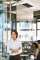 Businesswoman standing in office front view.