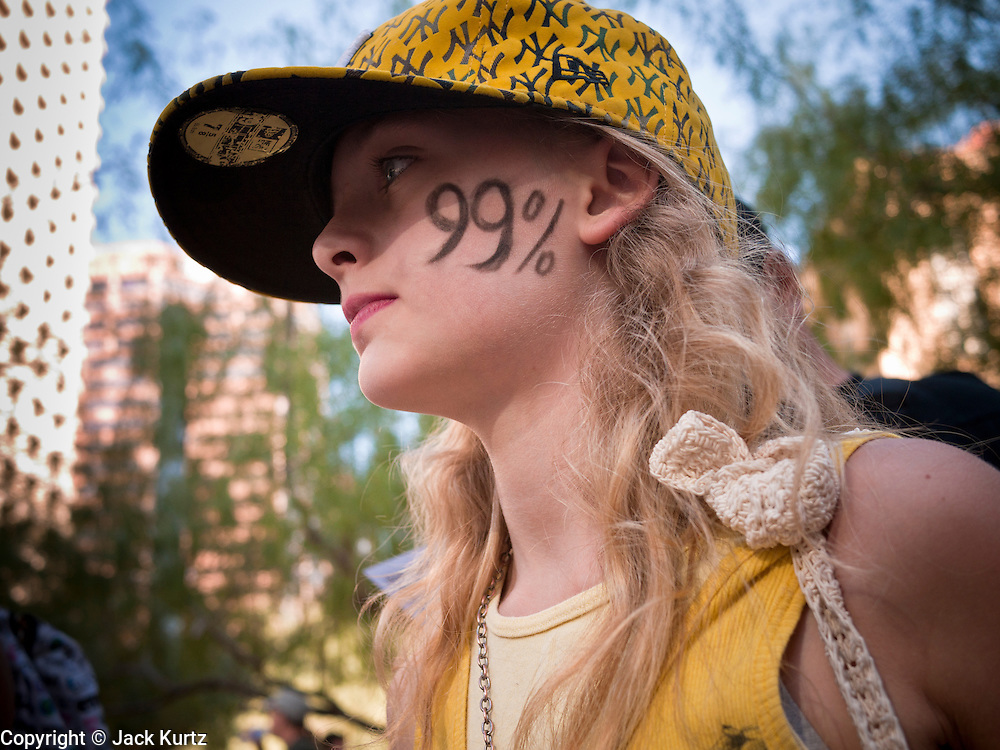 16 OCTOBER 2011 - PHOENIX, AZ: A girl at the Occupy Phoenix with 99% painted in her cheek in Phoenix, AZ, Sunday. About 200 people continued the Occupy Phoenix protest in downtown Phoenix Sunday afternoon. The protest peaked Saturday afternoon at about 2,000 people. Nearly 50 people were arrested late Saturday night on misdemeanor trespassing charges when they tried to camp in a park near downtown and on Sunday the crowd dwindled to 200. Protesters hope to continue the protest through Monday by marching around downtown and picketing banks in the area.   PHOTO BY JACK KURTZ