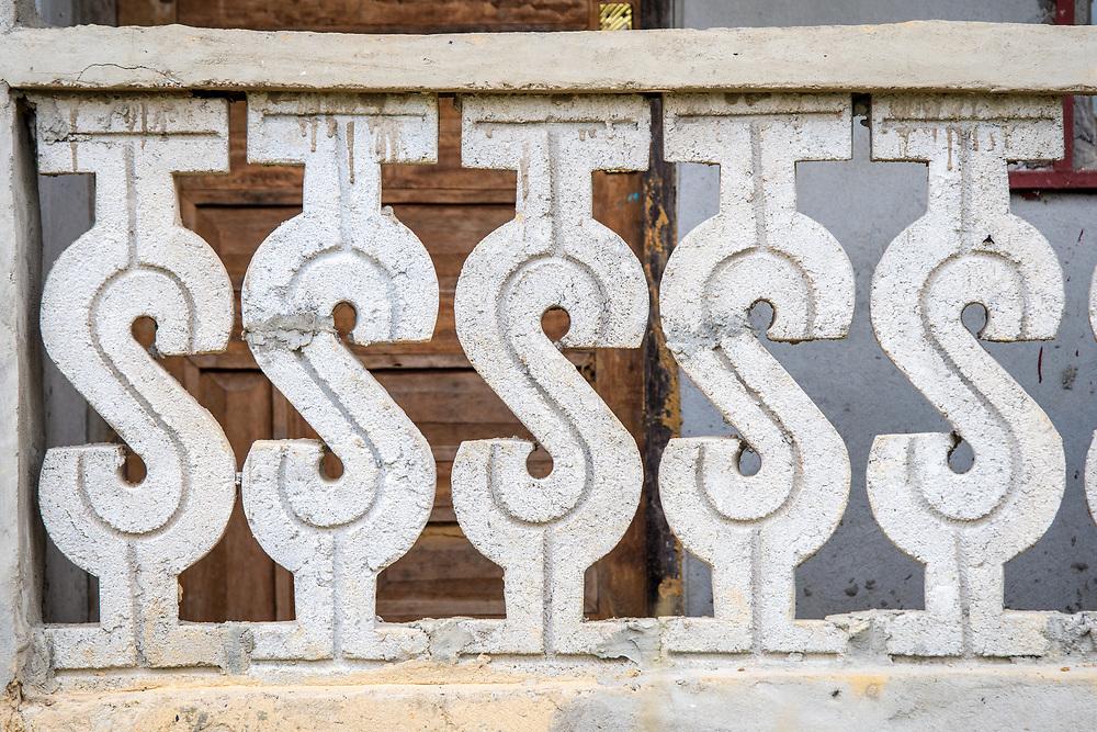 A stone fence is designed like dollar signs in Ganta, Liberia