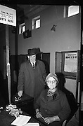President Eamon de Valera and An Taoiseach Seán Lemass cast their votes in the General Election. Picture shows Mrs. Lemass voting at Churchtown Schools, Dublin, watched by her husband.  .07.04.1965
